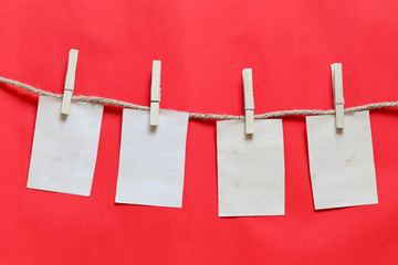 Blank brown note on clothesline and red background.