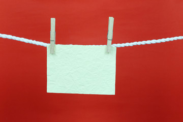 Empty note green paper hang on the clothesline and have copy space with red background.