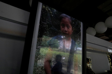 Boy is reflected in a picture of Jakelin Caal, a 7-year-old girl who handed herself in to U.S. border agents earlier this month and died after developing a high fever while in the custody of U.S. Customs and Border Protection, during a service at her home