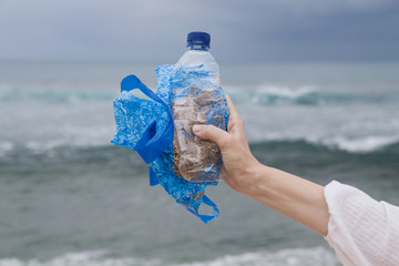 Plastic waste in hand against the blue sky background. The action of collecting trash from our beaches. Trash-free seas concept. Single-use plastic is a human addiction that is destroying our plan