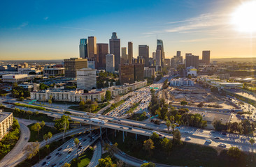 Drone view of downtown Los Angeles or LA skyline with skyscrapers and freeway traffic below. Wall mural