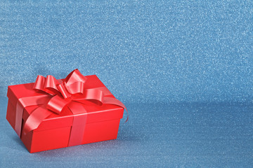 Closeup of a red box with a gift on a blue shiny background with copy space. Valentine's day celebration concept.