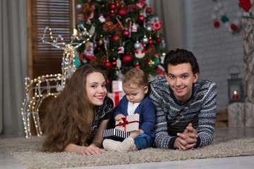 family sits with the baby sitting near the Christmas tree,