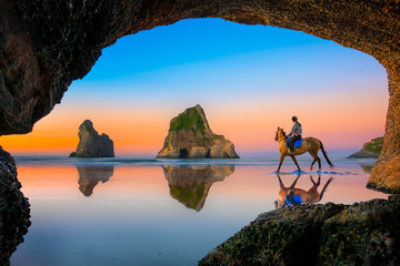 view from the cave of scenery view the sunset of Wharariki beach with Woman riding horse on the reflection beach, New zealand summer tourist popular place for vacation long weekend Wall mural