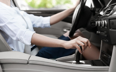 Businesswoman driving car and shifting automatic transmission