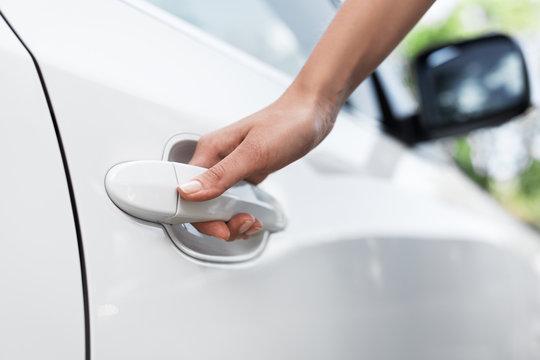 Business woman opening car door, holding handle