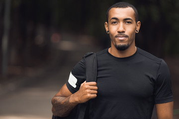 Muscular african-american man posing outside after workout