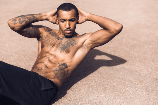 African-american man exercising sit ups on sports ground