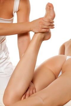 physiotherapist is stretching woman leg on physiotherapy session