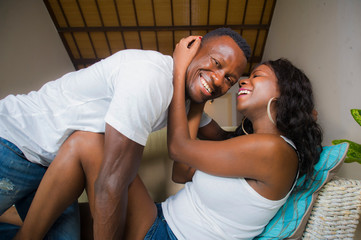 young attractive and happy romantic afro American couple in love lying playful cuddling at living room couch playing together enjoying beautiful relationship as cheerful lovers