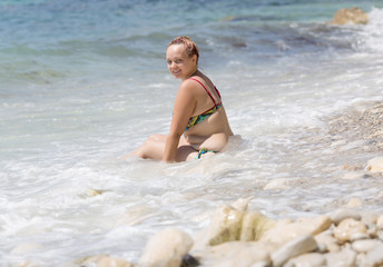 Overweight female person resting at the sea