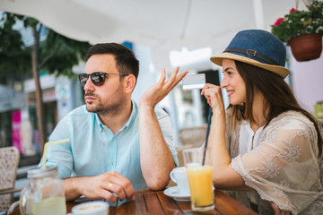 Beautiful loving couple sitting in a cafe enjoying in coffee and conversation, selective focus