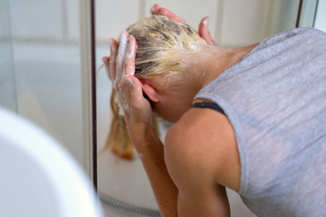 Blond woman shampooing her hair in a basin