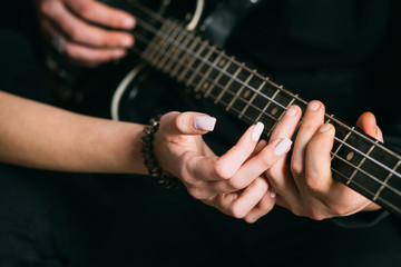 We love music. Couple in love play duets. Male and female hands play the electric guitar. Couple of guitar players. Couple of musicians enjoy playing music. Instrumental music live