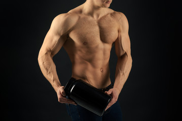 Diet for stronger body. Vitamin nutrition. Strong man hold vitamin bottles. Man with six pack abs. Muscle growing with anabolic steroids. Anabolic hormone increases muscle strength. Healthy diet