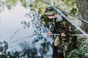Aged professional concentrated angler using fishing equipment