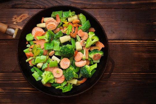 A mixture of frozen different vegetables in a pan on a wooden background.