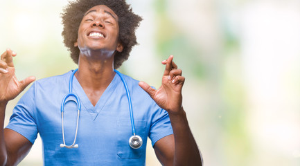 Afro american surgeon doctor man over isolated background smiling crossing fingers with hope and eyes closed. Luck and superstitious concept.