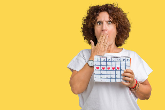 Middle ager senior woman holding menstruation calendar over isolated background cover mouth with hand shocked with shame for mistake, expression of fear, scared in silence, secret concept