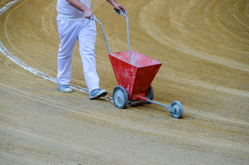 Arenero painting bullring lines in the sand