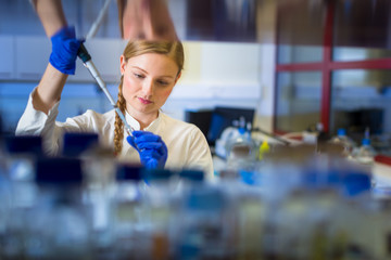 Female researcher carrying out research in a chemistry lab (color toned image; shallow DOF)