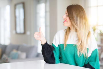 Young beautiful woman wearing winter sweater at home Looking proud, smiling doing thumbs up gesture to the side