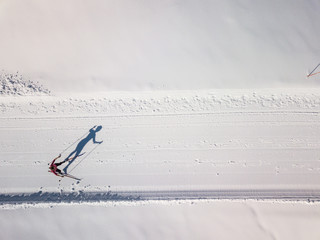 Cross-country skiing: young woman cross-country skiing on a winter day (motion blurred image) - aerial image