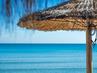 palms leafs straw parasol on the beach with blue sea in the background