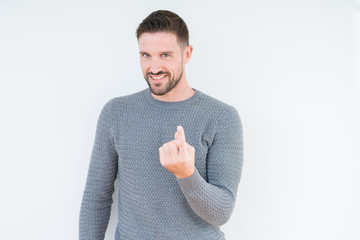 Young handsome man wearing casual sweater over isolated background Beckoning come here gesture with hand inviting happy and smiling