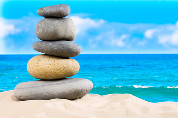 Zen rock, concept of harmony and balance. Zen stones pyramid on the beach with amazing turquoise blue water sea and sky