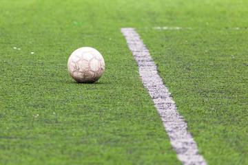 Ball on the green grass of a football field