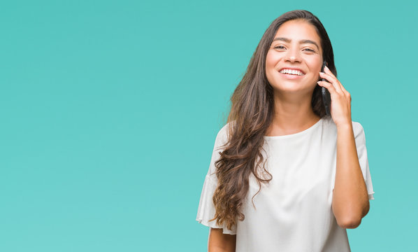Young beautiful arab woman talking on the phone over isolated background with a happy face standing and smiling with a confident smile showing teeth
