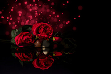 Red roses and heart shaped chocolates on black background