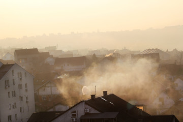Fototapeta Smoking chimneys at roofs of houses emits smoke, smog at sunrise, pollutants enter atmosphere. Environmental disaster. Harmful emissions and exhaust gases into air. Fog, winter day, heating season.