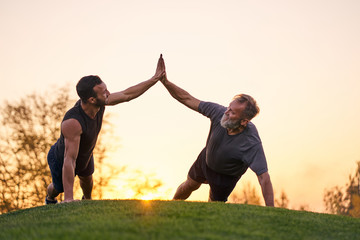 The two sportsmen push up together on the sunset background