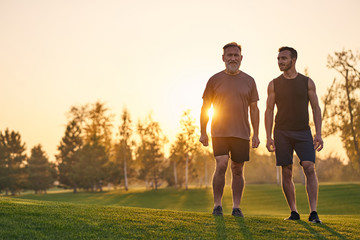 The two sportsmen standing on the grass on the sunset background