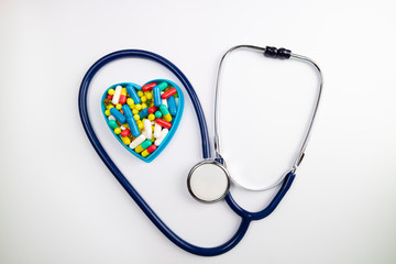 Stethoscope and heart of mixed pills. Medical background. Cardiovascular diseases, medicine and heath care concept