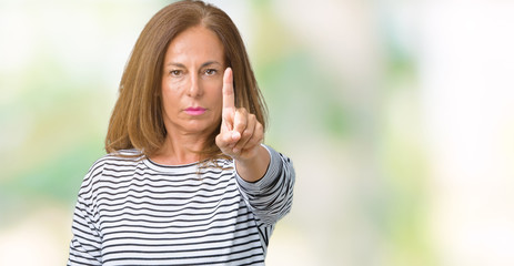 Beautiful middle age woman wearing stripes sweater over isolated background Pointing with finger up and angry expression