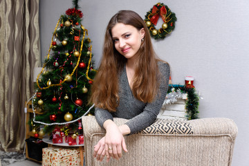 Young beautiful woman in a brilliant elegant evening dress, sitting near the Christmas tree and gifts on the eve of the new year