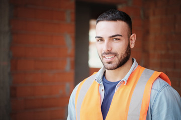 Young Construction Worker Smiling At Camera In New Building Wall mural