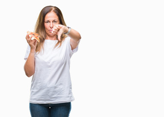 Middle age hispanic woman eating pizza slice over isolated background with angry face, negative sign showing dislike with thumbs down, rejection concept