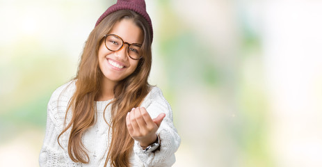 Young beautiful brunette hipster woman wearing glasses and winter hat over isolated background Beckoning come here gesture with hand inviting happy and smiling