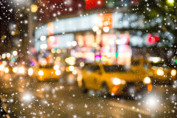 Defocused blur New York City  Manhattan street scene with yellow taxi cabs and snowflakes falling...