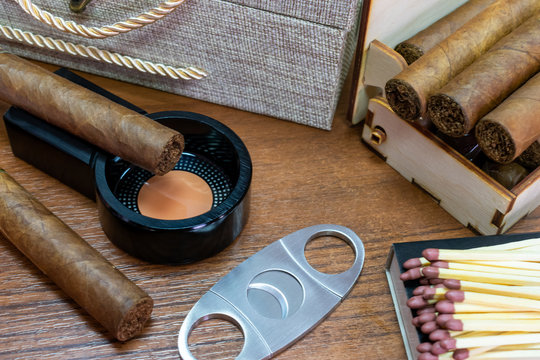 Brown cigar on a black ashtray. Vintage. Luxury. Bad habit. Smoking accessories on wooden background. A cigar humidor. Matches. Cutter.