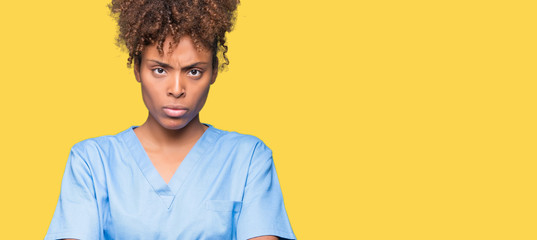 Young african american doctor woman over isolated background skeptic and nervous, disapproving expression on face with crossed arms. Negative person.