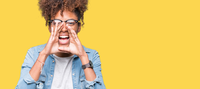 Beautiful young african american woman wearing glasses over isolated background Shouting angry out loud with hands over mouth