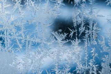 Frosty patterns on the frozen window are macro. Winter background