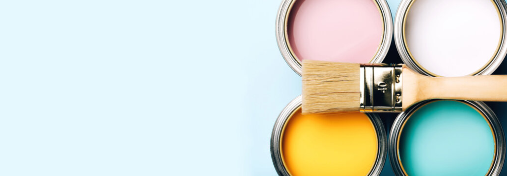 Banner of renovation concept. Brush with wooden handle on opened cans on blue pastel background. Yellow, white, pink, turquoise colors. Macro.