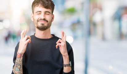 Young handsome man over isolated background smiling crossing fingers with hope and eyes closed. Luck and superstitious concept.