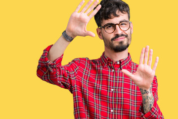 Young handsome man wearing glasses over isolated background Smiling doing frame using hands palms and fingers, camera perspective